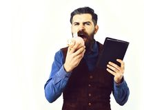 Bearded man holding notepad and moneybox with serious face. Bearded man, long beard, brutal caucasian hipster with moustache holding notepad and moneybox with Royalty Free Stock Photo