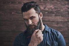 Man with beard. Bearded man is holding an old fashioned razor near his face and looking seriously at camera, on a wooden background royalty free stock photography