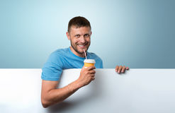 Bearded man holding a paper cup of drink with white banner Stock Images
