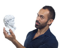 Bearded man holding a Roman bust Stock Photos