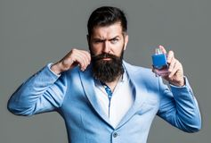 Bearded man holding up bottle of perfume. Fashion cologne bottle. Bearded male prefers expensive fragrance smell. Man stock photo