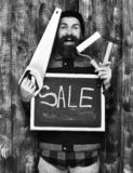 Bearded man holding various building tools and board, happy face. Bearded man, long beard, brutal caucasian hipster with moustache holding various building tools royalty free stock photo