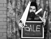 Bearded man holding various building tools and board, serious face. Bearded man, long beard, brutal caucasian hipster with moustache holding various building stock images