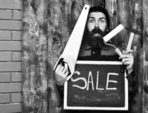 Bearded man holding various building tools and board, surprised face. Bearded man, long beard, brutal caucasian hipster with moustache holding various building stock images