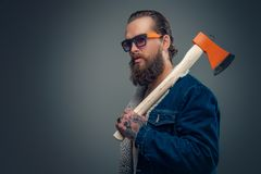 Bearded man holds an axe on his shoulder. Brutal bearded male with tattoos wearing denim coat and sunglasses holds an axe on his shoulder stock photos