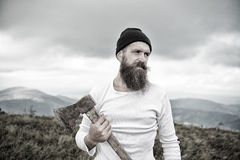Bearded man, holds axe on mountain top with cloudy sky. Hipster. bearded man, long beard, brutal caucasian hipster with moustache holds axe with serious face on Royalty Free Stock Image