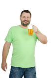 Bearded man holding lager mug. Cheerful bearded man in green t-shirt holding lager mug in left hand Royalty Free Stock Photos