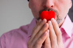 Bearded man holds red heart with fingers on his lips , Close up stock photos