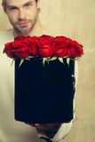 Bearded man holds red rose box on textured wall. Bearded macho man, brutal caucasian hipster with moustache in sweater and cap holds red rose flowers in box as Royalty Free Stock Photography