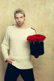 Bearded man holds red rose box on textured wall. Bearded macho man, brutal caucasian hipster with moustache in sweater and cap holds red rose flowers in box as Stock Images
