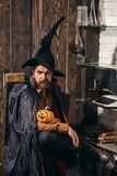 Bearded man with horror face holding Pumpkin head jack lantern on wood background. Holiday halloween with funny carnival. Costumes on a holiday background stock images