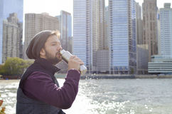 Bearded man hydrating at the urban area. With skyscraper background Royalty Free Stock Image