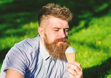 Bearded man with ice cream cone. Temptation concept. Man with beard and mustache on calm face enjoy ice cream, grass on. Background, defocused. Man with long royalty free stock photos