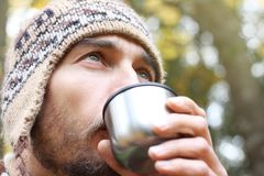 Bearded Man In Wool Knitted Hat Intently Drinks Hot Tea Or Coffee From Mug, Side View On Face, Background Of Forest Stock Photo