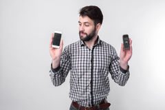 Bearded man isolated on a light background holding a modern smartphone and old cell phone with buttons Stock Image