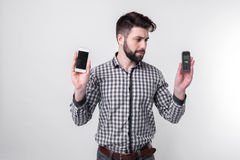 Bearded man isolated on a light background holding a modern smartphone and old cell phone with buttons Stock Images