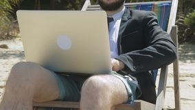 Bearded man in jacket and shorts is working on laptop on beach. During a vacation in summer in a southern country businessman controls business at a distance stock video
