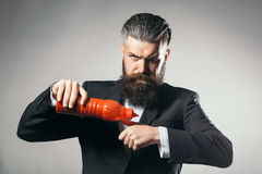 Bearded man with ketchup bottle Stock Images