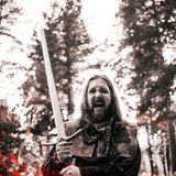 Battle cry, battle. Knight in the forest. Guy in medieval costume with sword. effect of fire and toning Royalty Free Stock Photography