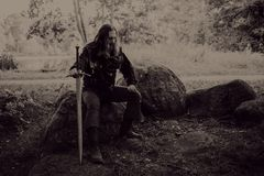 Knight in the forest. Guy in medieval costume with sword. effect of toning Stock Photos