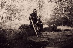 Knight in the forest. Guy in medieval costume with sword. effect of toning Stock Images