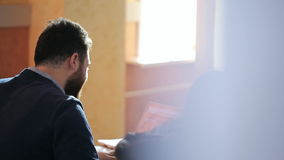 Bearded man with a laptop explains something to another male. A bearded man with a laptop explains something to another male. Perhaps it is the teacher and the stock video