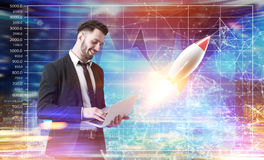 Bearded man with a laptop, graphs, rocket. Side view of a young bearded businessman holding a laptop and standing against a futuristic background with graphs and Stock Image