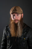 Bearded man with leather jacket and cap. A man with a long beard that has a streak in it is looking at the camera. He has a leather jacket and flat cap on royalty free stock photography