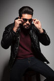 Bearded man in leather jacket is putting on his sunglasses Royalty Free Stock Image