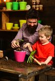 Bearded man and little boy child love nature. Father and son. Flower care watering. Soil fertilizers. happy gardeners. Bearded men and little boy child love royalty free stock photos