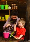 Bearded man and little boy child love nature. Father and son. Flower care watering. Soil fertilizers. happy gardeners stock photography