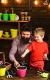 Bearded man and little boy love nature. happy gardeners with spring flowers. Father and son. Fathers day. Flower care. Bearded men and little boy love nature stock image