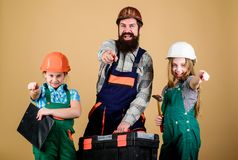 Bearded man with little girls. Father and daughter in workshop. Repairman in uniform. Foreman. construction worker. Assistant. Builder or carpenter. Family royalty free stock images