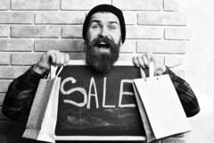 Bearded hipster holding shopping packages and board with Sale inscription. Bearded man, long beard. Brutal caucasian happy hipster with moustache holding stock photo
