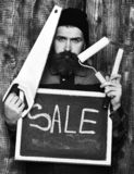 Bearded man holding various building tools and board, serious face. Bearded man, long beard, brutal caucasian hipster with moustache holding various building royalty free stock image