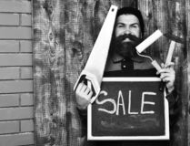 Bearded man holding various building tools and board, happy face. Bearded man, long beard, brutal caucasian hipster with moustache holding various building tools stock photography