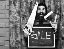 Bearded man holding various building tools and board, happy face. Bearded man, long beard, brutal caucasian hipster with moustache holding various building tools royalty free stock image