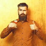 Bearded man, long beard. Brutal caucasian serious hipster with moustache in brown shirt holding alcoholic red shot on royalty free stock photo