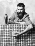 Brutal caucasian hipster holding tropical alcohol fresh cocktail. Bearded man, long beard. Brutal caucasian shouting tattooed hipster with moustache in denim royalty free stock image