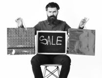 Bearded man, brutal caucasian hipster with moustache holding shopping packages. Bearded man, long beard. Brutal caucasian squinting hipster with moustache stock images