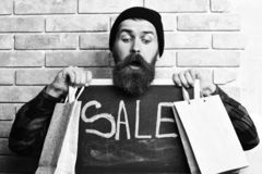 Bearded hipster holding shopping packages and board with Sale inscription. Bearded man, long beard. Brutal caucasian surprised hipster with moustache holding royalty free stock photography