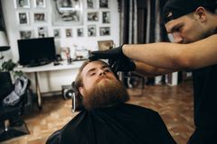 Bearded man with long beard getting stylish hair shaving , haircut , with razor by barber in barbershop stock image