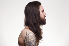 Bearded man with long hair and tattoo. Tattooed handsome bearded man with long hair.Brutal hipster boy with tattoo royalty free stock image