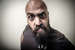 Bearded man looking camera with funny strange expression Stock Image