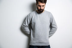 Bearded man looking down. Bearded man in grey shirt with long sleeves looking down on grey background. Mock up Stock Image