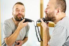 Man shaving trimming his beard stock image