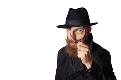 Bearded man looking through a magnifying glass. Stock Photography