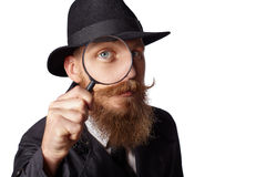 Bearded man looking through a magnifying glass. Stock Image