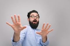 Scared man gesturing with hands on gray. Bearded man looking terrified and protecting with hands outstretched forward looking at camera Royalty Free Stock Photo