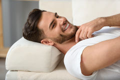 Bearded man lying on a couch royalty free stock photography